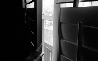 black and white image of hand opening window shutters