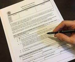 hand filling out application for citizenship
