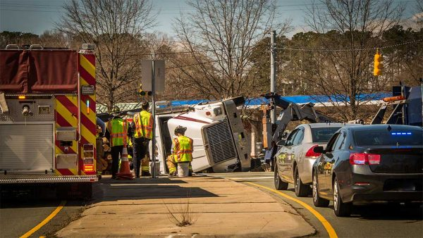 commercial truck tipped over in accident with cars backed up and emrgency vehicle on site