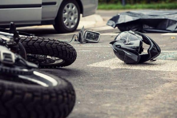 low view of street and auto accident with fallen motorcycle, motorcycle helmet, car debris, and car in the background