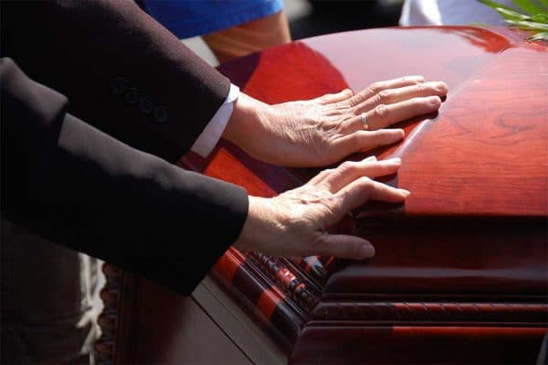 hands touching a coffin during a funeral